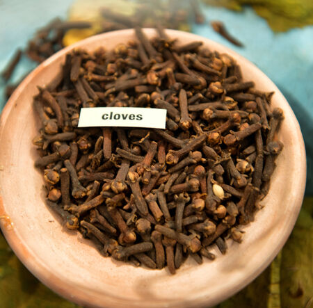 pungent: Vista dall'alto di un piatto di chiodi di garofano in polvere, un forte spezia piccante a base di germogli di fiori secchi di Syzygium aromaticum