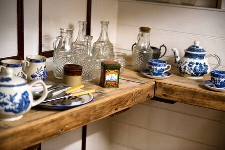 sark: Display of crockery and cutlery on the Cutty Sark with blue and white pottery, plates, glassware and utensils on a wooden table