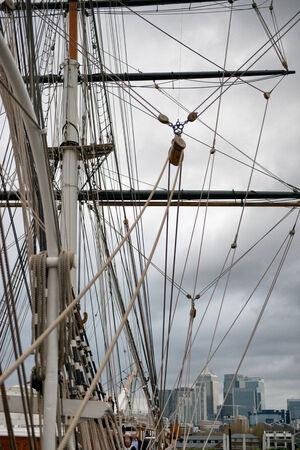 pulleys: Aparejo de la Cutty Sark, un viejo clipper comerciante victoriano, con los largueros, m�stil y poleas y una vista de la ciudad de Londres en el fondo Editorial