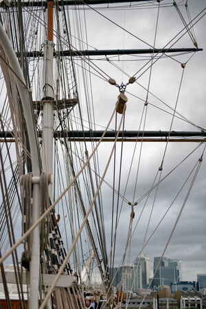 pulleys: Rigging of the Cutty Sark, an old Victorian merchant clipper, with the spars, mast and pulleys and a view of the city of London in the background