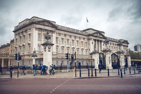 Buckingham Palace with Main Gate under gray sky in London, England