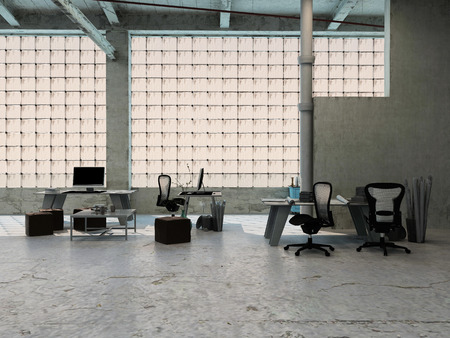 Small office area in an industrial loft with tables, stools, chairs and equipment arranged in front of large windows