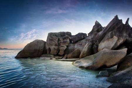 Aantrekkelijke Spot van enorme rotsen op de Seychellen aan de zijkant van Beautiful Blue Water Zee. Gevangen op Gradient blauwe hemel boven.