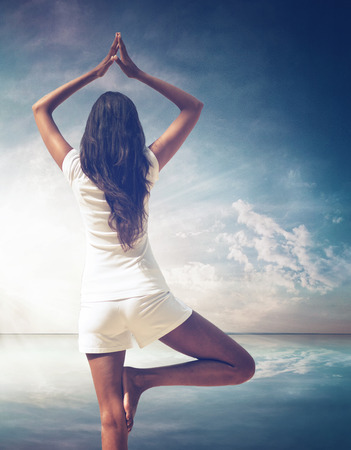 Long Hair Woman Doing Yoga Pose with Overhead Hands and Lifted Foot, Facing Backward on Illuminated Abstract Light Background. photo