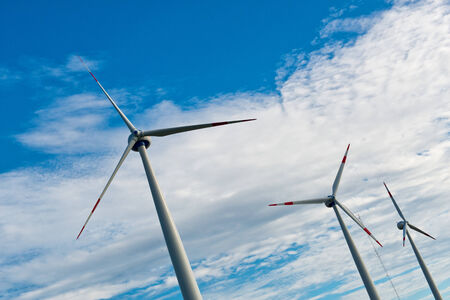 Row of wind turbines on a wind farm generating, sustainable renewable energy and electricity from the kinetic energy of the wind against a cloudy blue sky photo
