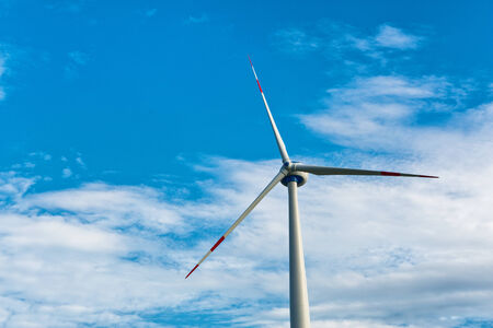 Single wind turbine providing sustainable energy and electricity by converting the kinetic energy of the wind using a natural resource against a blue sky with copyspace photo