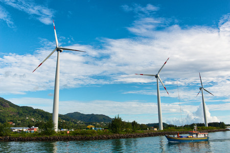Boat passing in front of three wind turbines sited on the edge of the sea providing electricity from the conversion of the kinetic energy of the wind, scenic coastal view with a hamlet behind photo