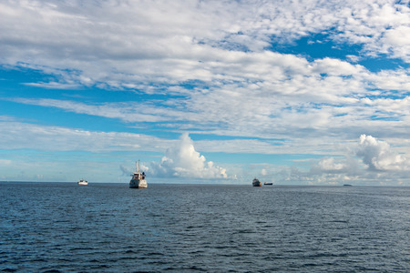 nave: Sea Vessels sailing on Beautiful Blue Water Ocean in Seychelles Islands. Captured with Dramatic Clouds Above on a Tropical Climate.
