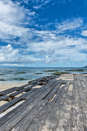 ramshackle: Dilapidated wooden boardwalk at Anse Union beach in the Seychelles with missing and broken planks extending along a pier to the ocean Stock Photo