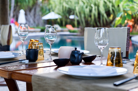 Close Up of Table Place Settings at Outdoor Poolside Asian Restaurant Archivio Fotografico