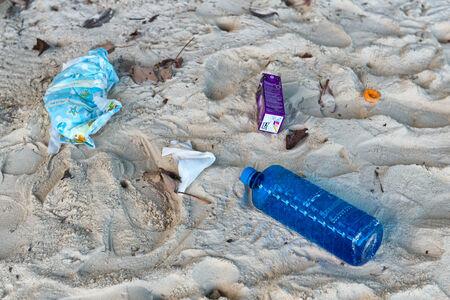 botar basura: Contaminación Basura varado en la arena de la playa, como botellas de plástico y cajas de bebidas alcohólicas