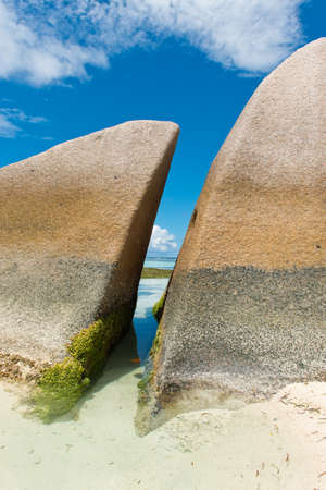 Algae on Historic Huge Rocks, with Blue and White Sky Background, at Anse Source dArgent Lagoon. Located in La Digue Island, Seychelles. photo