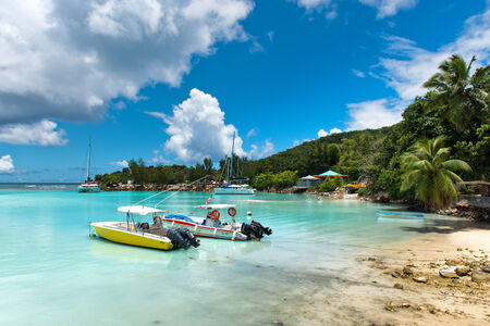 sheltered: Small boats in the harbor at La Digue, Seychelles , moored alongside the golden sand of a tranquil tropical beach in a sheltered lagoon