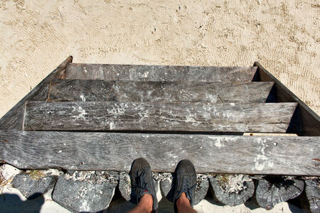 Looking Down at Feet Standing on Wooden Steps Leading Down to Beach photo