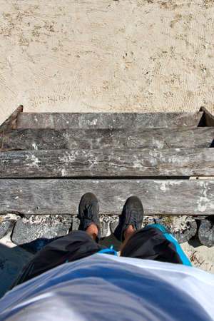 Looking Down at Man Standing on Wooden Steps Leading Down to Beach Stock Photo