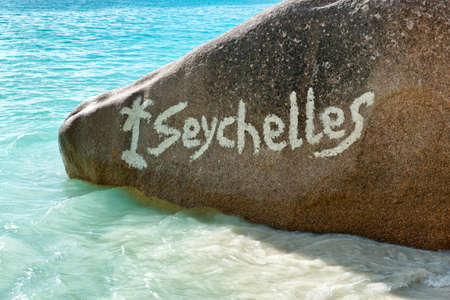 oceanic: Close up Seychelles Text on Granite Rock at Anse Lazio Beach, Praslin Island. Stock Photo