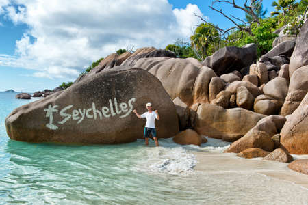 huge: Enthusiastic Man Standing Beside Boulder Formation on Seychelles Beach