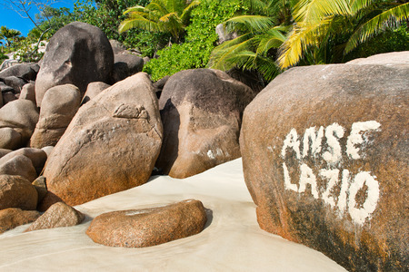 Painted sign on a rock for Anse Lazio, Seychelles, marking the idyllic tropical beach on the island with its golden sand and granite boulders photo