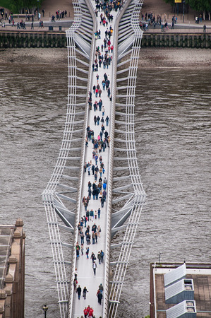 Random People Passing at Famous Millennium Bridge at River Thames in London. Captured in Aerial View. photo