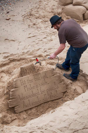 southbank: Artist working on a sand sculpture with a motivational message on a set of wooden planks on the south bank of the River Thames, London Editorial
