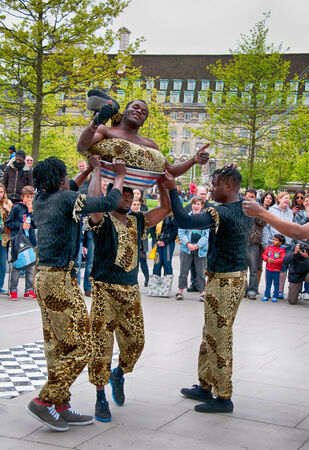 Group of Jamaican street performers and acrobats giving a performance for a group of people at Southbank, London, England Editorial