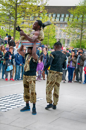 southbank: Group of Jamaican street performers and acrobats giving a performance for a group of people at Southbank, London, England Editorial