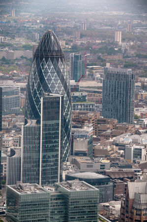 the gherkin: Aerial view of the modern design and architecture of the Gherkin in the London CBD and a rooftop view of surrounding buildings