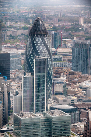 Aerial view of the modern design and architecture of the Gherkin in the London CBD and a rooftop view of surrounding buildings