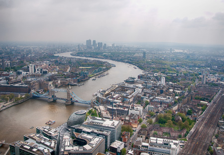 aerial animal: Overview of London and the River Thames as it winds its way through the buildings of the city on a cold grey day with the Tower Bridge in the foreground