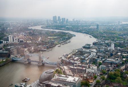 Luchtfoto van de rivier de Theems kronkelende door de stad van Londen met de Tower Bridge op de voorgrond op een grijze mistige dag