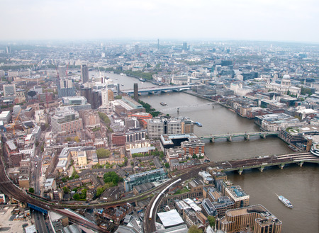 Aerial view of London and the bridges over the River Thames showing the topography of the city on a cloudy day photo