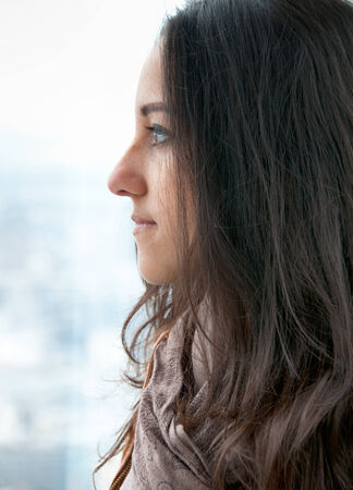 introspective: Side portrait of a beautiful young brunette woman looking through a glass window, with a wistful facial expression, in a cold day