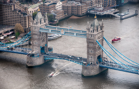 Aerial View of Famous Historic Tower Bridge at River Thames in London. Captured with Small Boats Passing by the River. photo
