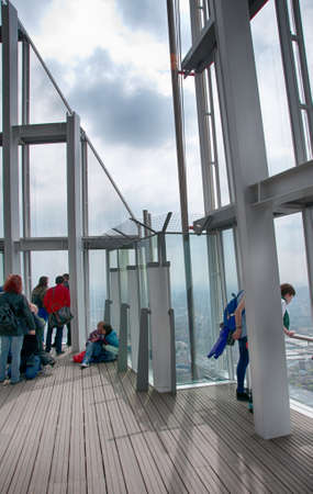 shard of glass: Tourists sightseeing on the observation deck of the Shard in London, England standing looking out from the glass sides