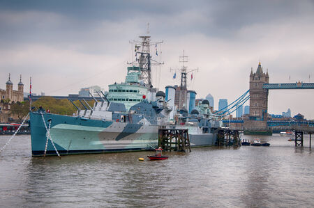 HMS Belfast battleship, now a museum exhibit, moored in the River Thames with the Tower Bridge behind