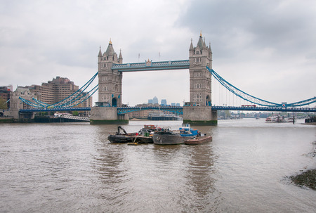 Small Vintage Boats at River Thames in London with Famous Historic Tower Bridge Background. photo