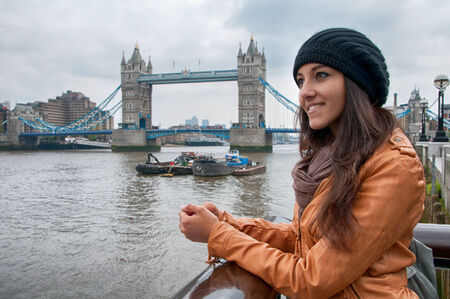 gothic woman: Fashionable young Asian woman sightseeing in London standing at a railing overlooking the River Thames and Tower Bridge on a grey cloudy day