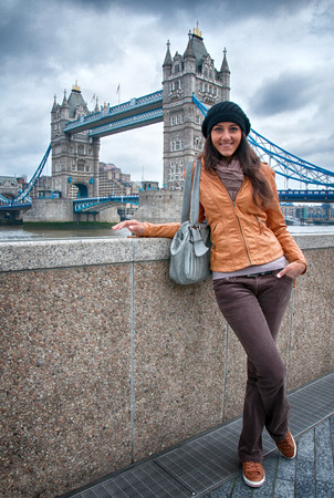 Pretty Smiling Young Woman in Casual Attire Posing with Famous Tower Bridge Background in London. photo