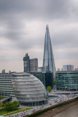 pyramidal: View of the domed structure of the City Hall and pyramidal Shard in London against a cloudy sky Stock Photo