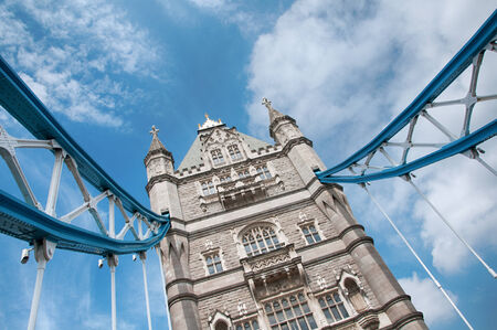 western europe: Detail of one of the towers on Tower Bridge, London with a portion of the suspension cables against a cloudy blue sky
