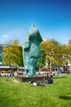 Statue of a horse head by Nic Fiddian-Green in Hyde Park, London patinated by green verdigris with people relaxing on the green grass surrounding it