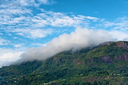 blanketed: Morne Seychellois, the highest mountain peak on Mahe, Seychelles, blanketed in low lying cloud cover under a cloudy blue sky