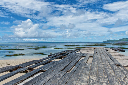 Dilapidated wooden boardwalk at Anse Union beach in the Seychelles with missing and broken planks extending along a pier to the ocean photo