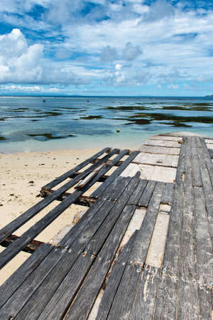 union beach: Stone pier with a dilapidated wooden boardwalk with missing boards on the beach at Anse Union, Seychelles Stock Photo