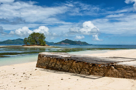 union beach: Old stone pier rising above the golden sand of the beach at Anse Union, La Digue under a cloudy blue summer sky Stock Photo