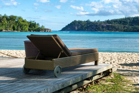 deck chair: Luxury Lounge Chair on Wooden Deck Facing Beach and Mountains, Port Launay, Seychelles