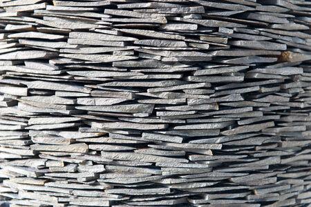 shingles: Pila de tejas de piedra tallada a mano de la roca de pizarra en una pared de piedra seca formación