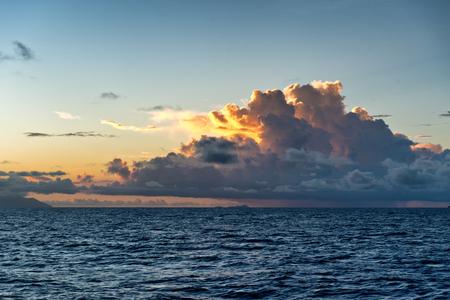 towering: Colorful orange tropical sunset behind cumulonimbus clouds towering above a calm blue ocean Stock Photo