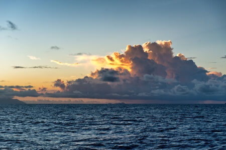 squall: Colorful orange tropical sunset behind cumulonimbus clouds towering above a calm blue ocean Stock Photo