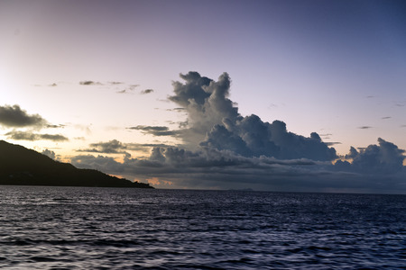 Colorful tropical sunset behind cumulonimbus clouds towering above a calm blue ocean photo